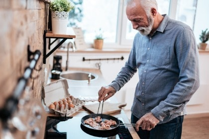 smiling-senior-man-cooking-bacon-eggs-for-keto-breakfast